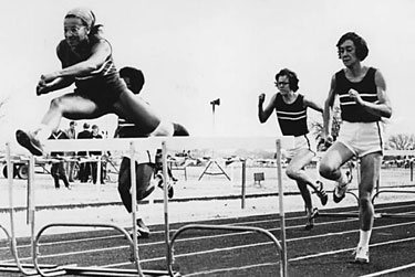 Athletes in hurdle race, track and field competition